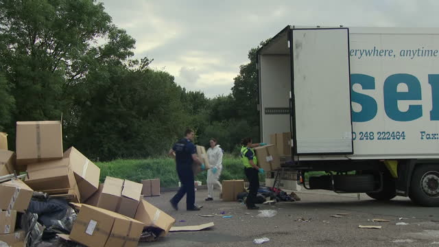 exterior shots of police officers at the scene where thirteen men and boys were discovered in the back of a lorry at a service station including... - trafficking stock videos and b-roll footage