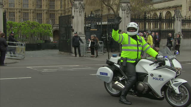 exterior shots of police officers outside the palace of westminster opening the barriers outside the carriage gate and allowing a series of police... - motorcade stock videos & royalty-free footage