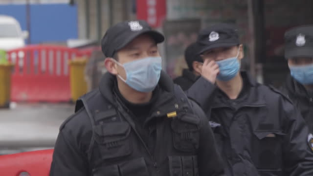vídeos de stock, filmes e b-roll de exterior shots of police officers wearing hygiene masks standing in the street following the city being put on lockdown shots of the wuhan seafood... - confinamento
