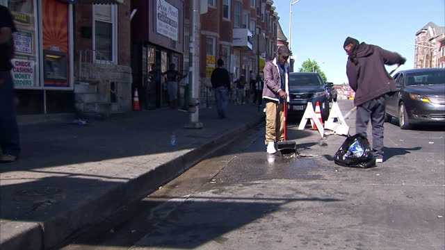 stockvideo's en b-roll-footage met exterior shots of police stood in the street with riot shields and helmets as workers clean up debris from the previous night's unrest on april 29... - maryland staat