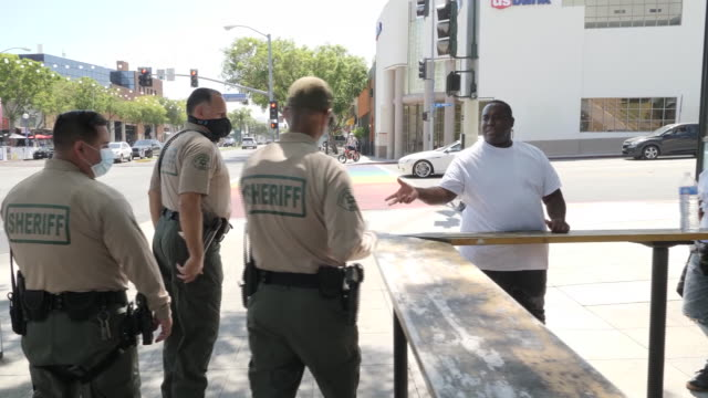 exterior shots of police walking on patrol wearing face masks passing route 66 signs in lgbt rainbow colours and various shops and cafes, stopping to... - west hollywood stock-videos und b-roll-filmmaterial