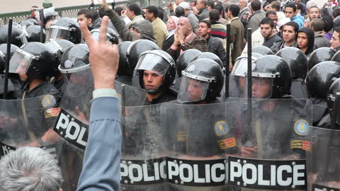 exterior shots of police wearing riot protection & holding riot shields walk in formation towards hundreds of protesters in the street on january 28,... - egypt stock videos & royalty-free footage