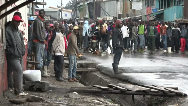 Exterior shots of police with riot gear on the streets of a slum in a stand off with protesters with tyres burning in the road amid violence in the...
