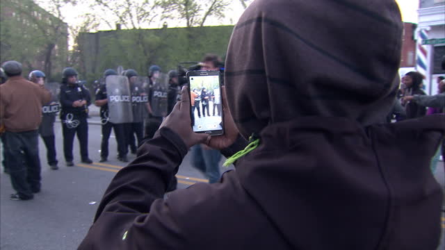 exterior shots of police with riot shields in a stand off with a male protester on april 28, 2015 in baltimore, maryland. - 2015 video stock e b–roll