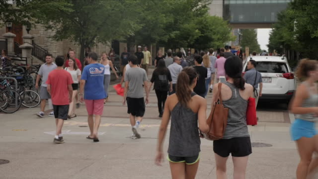 exterior shots of political canvassars on the university of madison wisconsin handing out flyers urging students to register to vote in the run up to... - ウィスコンシン州点の映像素材/bロール