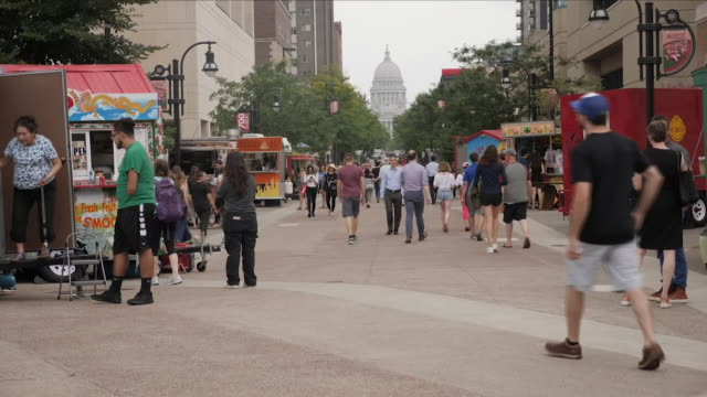 exterior shots of political canvassars on the university of madison wisconsin handing out flyers urging students to register to vote in the run up to... - wisconsin stock videos & royalty-free footage