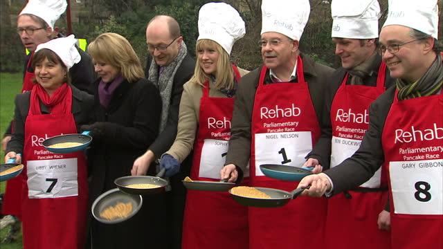 exterior shots of political reporter sophie ridge competing in annual pancake race against other reporters and mp's on abingdon green shrove tuesday... - パンケーキ点の映像素材/bロール