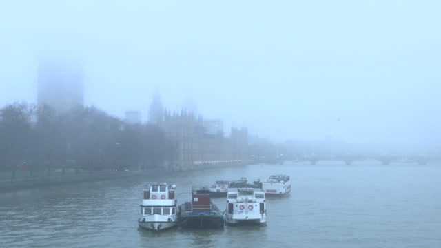 Exterior shots of poor visibility across London landmarks obscured by thick fog including Houses of Parliament the London Eye and the Victoria Tower...