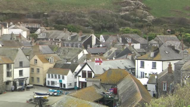 exterior shots of port isaac beach houses going up steep hill and a seagull soaring above rooftops on 3 april 2019 in port isaac united kingdom - steep stock videos & royalty-free footage