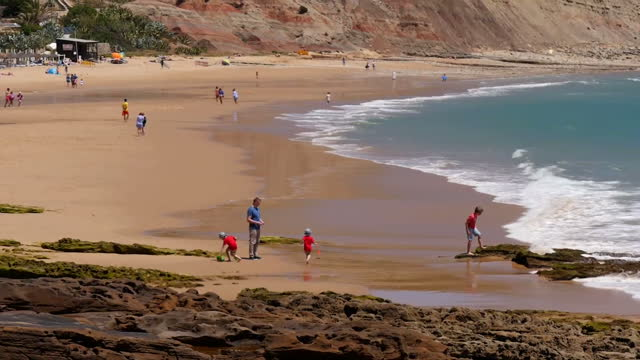 exterior shots of praia da luz beach with tourists walking and sunbathing ten years to the day since the disappearance of madeleine mccann on 3 may... - madeleine mccann video stock e b–roll
