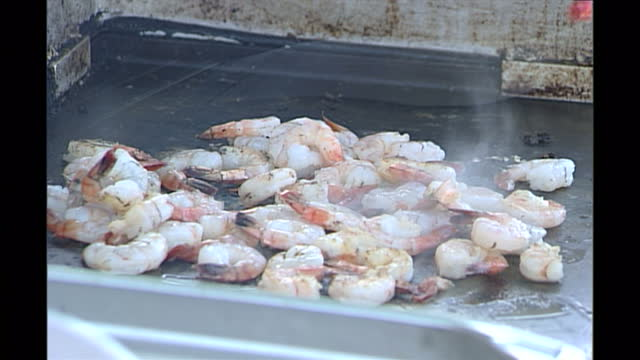 stockvideo's en b-roll-footage met exterior shots of prawns being cooked on a beach barbecue on australia's gold coast on february 2nd 2002 in brisbane australia - steurgarnaal