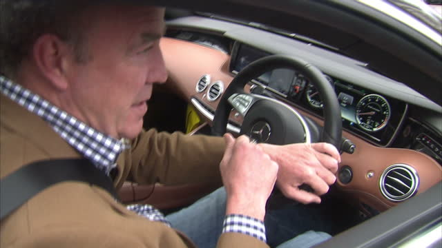 exterior shots of presenter and columnist jeremy clarkson departing from his london home and being mobbed by journalists and paparazzi as he drives... - jeremy clarkson stock-videos und b-roll-filmmaterial