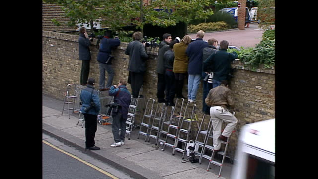 Exterior shots of press and paparazzi standing on ladders looking over wall outside gym where Princess Diana Princess of Wales is attending...