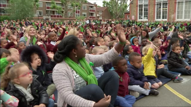 exterior shots of primary school children seated outside during a memorial service to mark the one year anniversary of the grenfell tower fire... - トリビュート・イベント点の映像素材/bロール