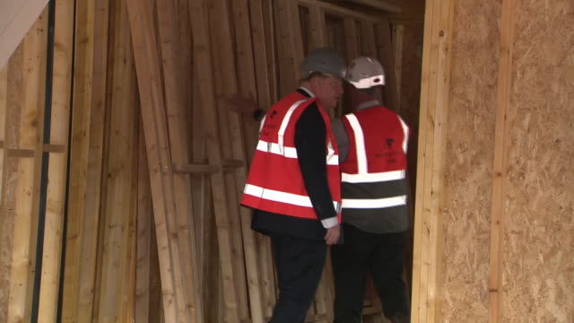 exterior shots of prime minister boris johnson wearing a hardhat and high visibility and speaking with workers as he tours a housing development... - kopfbedeckung stock-videos und b-roll-filmmaterial