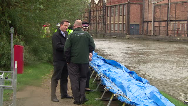 exterior shots of prime minister david cameron meeting officials and environment agency workers during a visit to view flood defence measure being... - david cameron politician stock videos & royalty-free footage