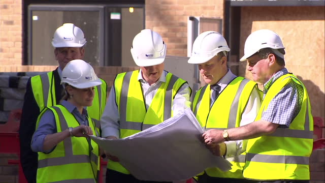 Exterior shots of Prime Minister David Cameron walking on a tour of a new housing estate with officials wearing a hard hat and high visibility jacket...