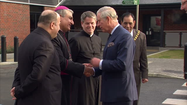 Exterior shots of Prince Charles arriving at the Church of the Holy Family in Acton and meeting local officials and members of the clergy including...