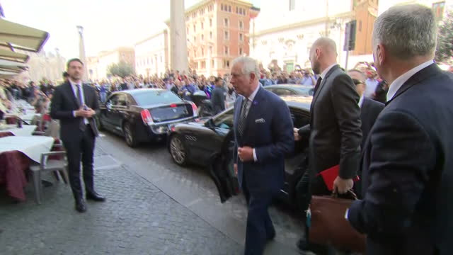 Exterior shots of Prince Charles arriving to visit the Vatican and being surrounded by crowds of security and the media as he greets local people and...