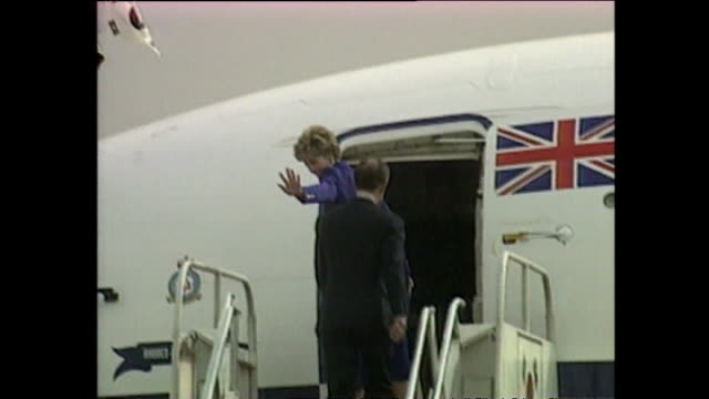 vídeos de stock e filmes b-roll de exterior shots of prince charles, prince of wales, and princess diana, princess of wales, walk along red carpet with guard of honour at airport as... - 1992