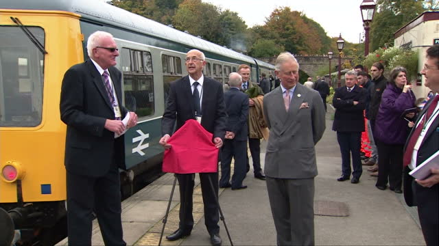 exterior shots of prince charles, prince of wales unveils a plaque with a flourish as he visits wirksworth station on the ecclesbourne valley... - ダービーシャー点の映像素材/bロール