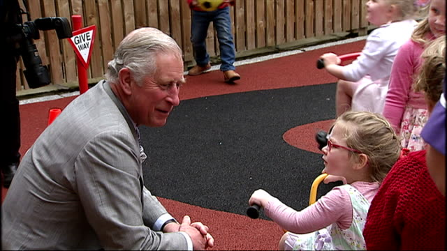 exterior shots of Prince Charles Prince of Wales walking into nursery playground and talk to children and staff at the East Belfast Network Centre on...