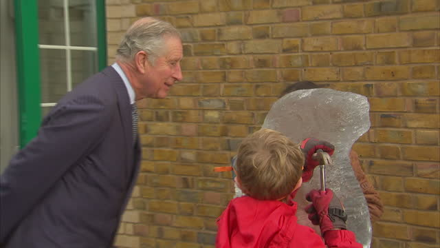 Exterior shots of Prince Charles speaking with teachers and children in playground of Ashley Church of England Primary School as students make an ice...