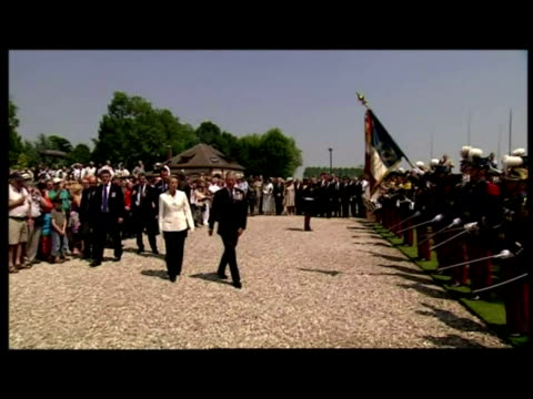 Exterior shots of Prince Charles stood with unknown official in front of French troops as British national anthem is played Exterior shots of Prince...