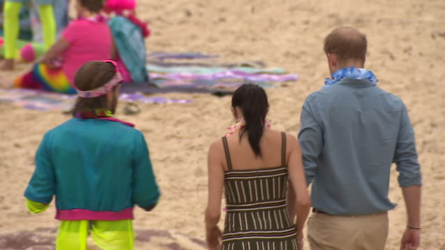 exterior shots of prince harry and meghan, duchess of sussex stepping bare foot on bondi beach in floral garlands and joining joined surfing group... - barefoot stock videos & royalty-free footage