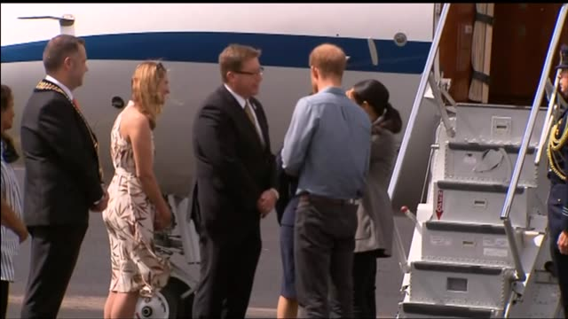 exterior shots of prince harry and meghan duchess of sussex walking from plane to aircraft hangar on arrival at the royal flying doctor service... - meghan duchess of sussex stock videos and b-roll footage