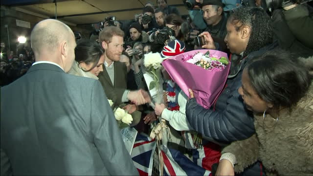 vídeos de stock, filmes e b-roll de exterior shots of prince harry and meghan markle greeting enthusiastic members of the public and being presented with bunches of flowers by... - brixton
