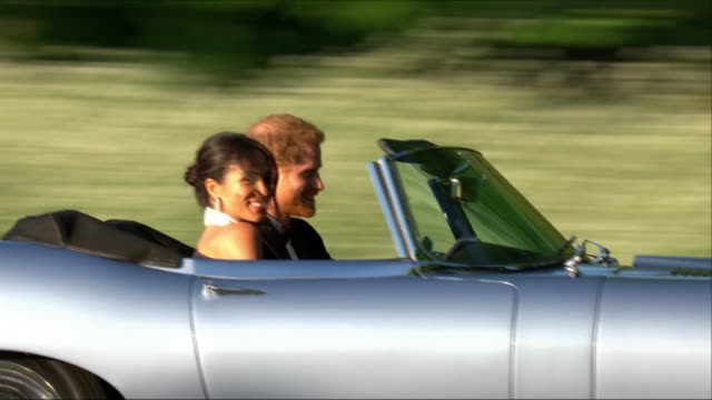 Exterior shots of Prince Harry and Meghan Markle leaving Windsor Castle and getting into an open top EType Jaguar and departing the Castle for...