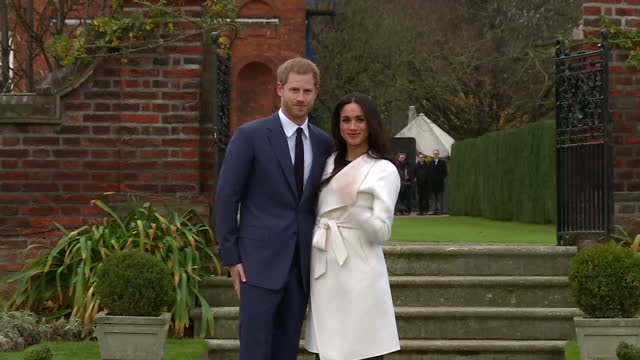 vídeos de stock, filmes e b-roll de exterior shots of prince harry and meghan markle posing for a photocall after the announcement of their engagement then walking away together through... - meghan harry