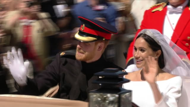 Exterior shots of Prince Harry and Meghan Markle waving to cheering crowds as the Royal carriage procession goes along Kings Road after the Wedding...