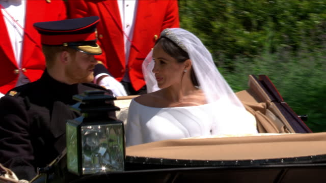 Exterior shots of Prince Harry and Meghan Markle waving to crowds and fans from the Ascot Landau carriage as they depart Windsor Castle and out of...