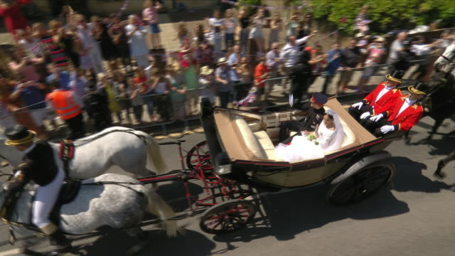 Exterior shots of Prince Harry and Meghan Markle waving to crowds and fans from the Ascot Landau carriage as they travel along Kings Road during the...