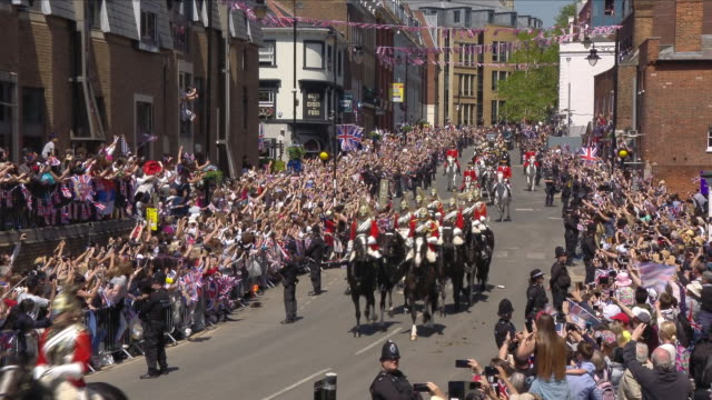 Exterior shots of Prince Harry and Meghan Markle waving to crowds and fans from the Ascot Landau carriage as they travel along the Sheet Street and...
