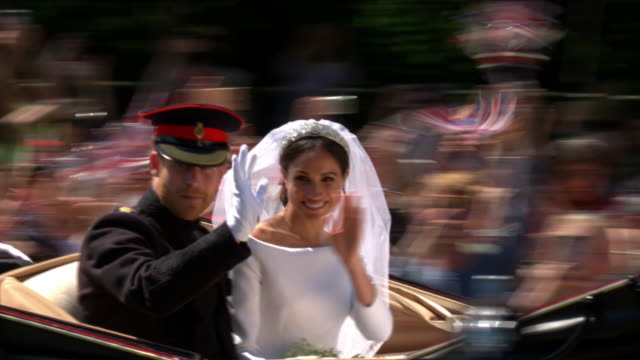 Exterior shots of Prince Harry and Meghan Markle waving to crowds and fans from the Ascot Landau carriage as they travel along The Long Walk and...