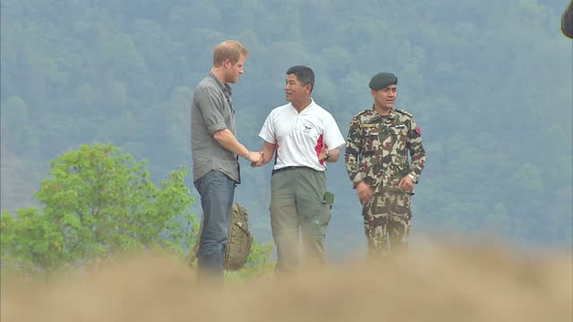 exterior shots of prince harry arriving at bardia via helicopter and greeting local people being presented with garlands on march 21 2016 in... - nepal stock-videos und b-roll-filmmaterial