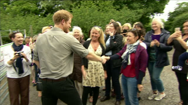 Exterior shots of Prince Harry arriving to greet a group of women one asking for a kiss and Prince Harry refuses and Prince Harry helping plant a...