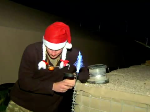 exterior shots of prince harry captain wales turning on miniature christmas tree lights at camp bastion with photographer taking pictures prince... - prinz königliche persönlichkeit stock-videos und b-roll-filmmaterial