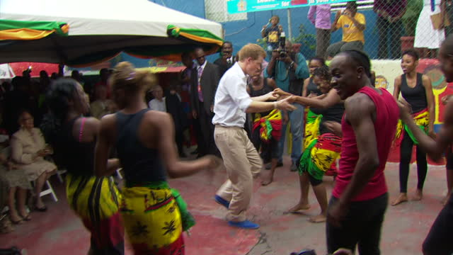 exterior shots of prince harry dancing with children at bustamente hospital in kingston. prince harry wears blue suede shoes & is on a four day visit... - jamaica stock videos & royalty-free footage