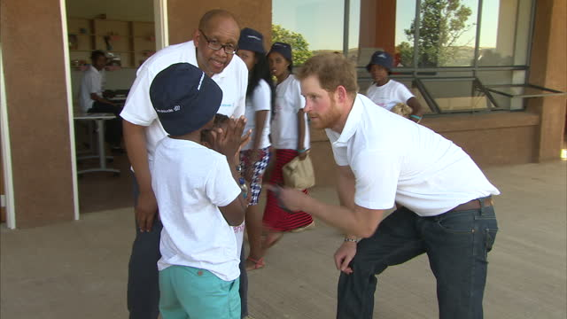 exterior shots of prince harry meeting young people on a visit to the sentebale children's home in lesotho on november 26 2015 in maseru lesotho - waisenhaus stock-videos und b-roll-filmmaterial