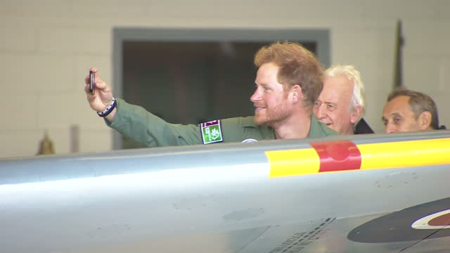 exterior shots of prince harry taking a selfie photo of himself in front of a ww2 spitfire as it is driven out of a hangar during the battle of... - military aeroplane stock videos & royalty-free footage