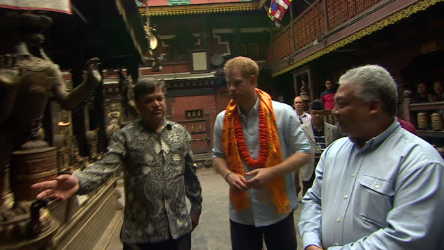 exterior shots of prince harry visiting a temple in patan durbar square and lighting a votive candle>> on march 20 2016 in kathmandu nepal - votive candle stock videos and b-roll footage