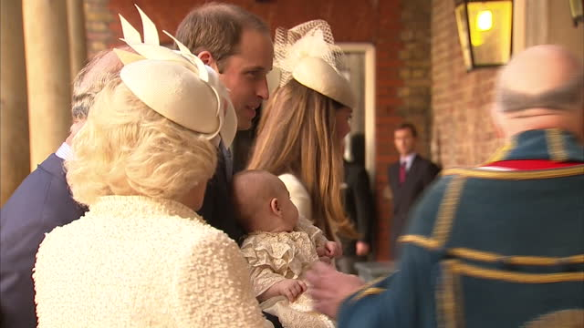 exterior shots of prince william carrying prince george of cambridge and catherine duchess of cambridge walk into chapel royal followed by rest of... - baptism stock videos & royalty-free footage