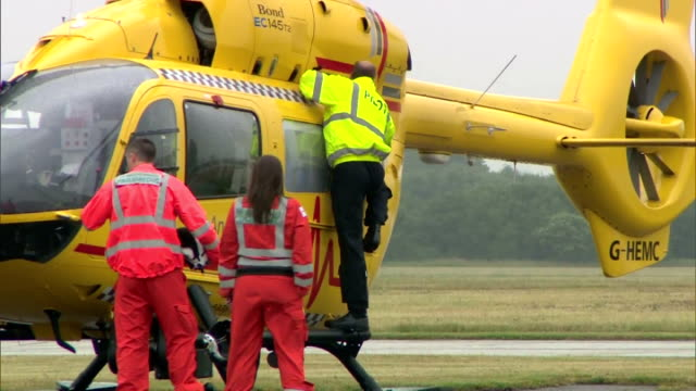 vídeos y material grabado en eventos de stock de exterior shots of prince william duke of cambridge at work performing last minute checks on an east anglian air ambulance on july 13 2015 in... - 2015