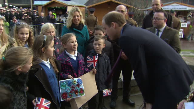 exterior shots of prince william duke of cambridge talking to children and looking at their artwork children handing him christmas decorations at the... - the victoria cross stock-videos und b-roll-filmmaterial