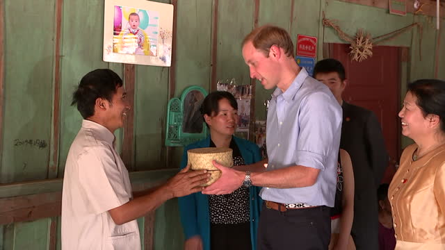 vídeos de stock, filmes e b-roll de exterior shots of prince william exchanging gifts with a local family and eating a local delicacy on march 4 2015 in xishuangbanna china - yunnan province