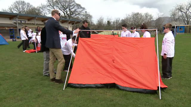 exterior shots of prince william taking part in a teamwork exercise putting on a blindfold as a group of children try to construct a tent following... - festzelt stock-videos und b-roll-filmmaterial